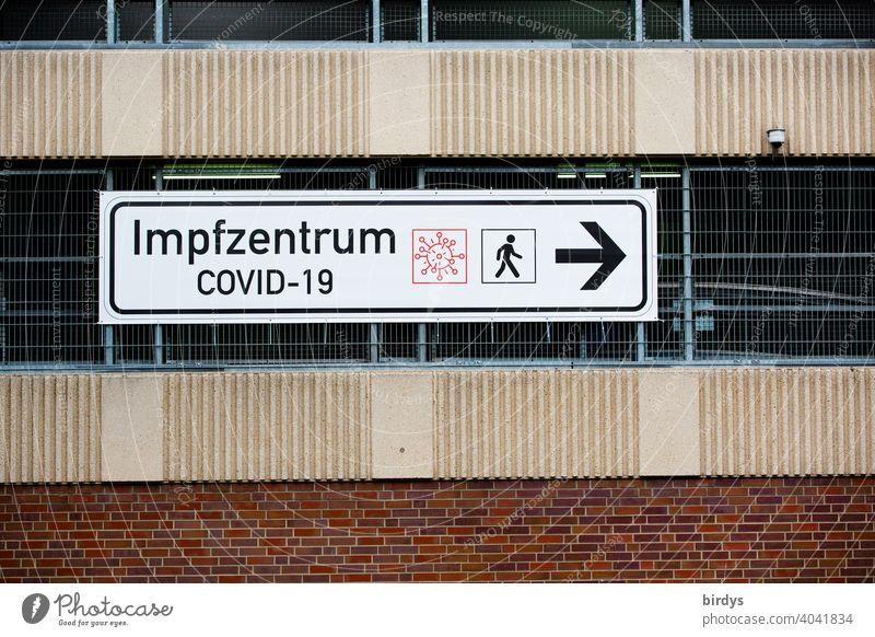 Wegweiser zum Covid-19 Impfzentrum. Impfzentrum ,großes Hinweisschild an einem Parkhaus impfzentrum covid-19 impfen pandemie wegweiser hinweisschild corona