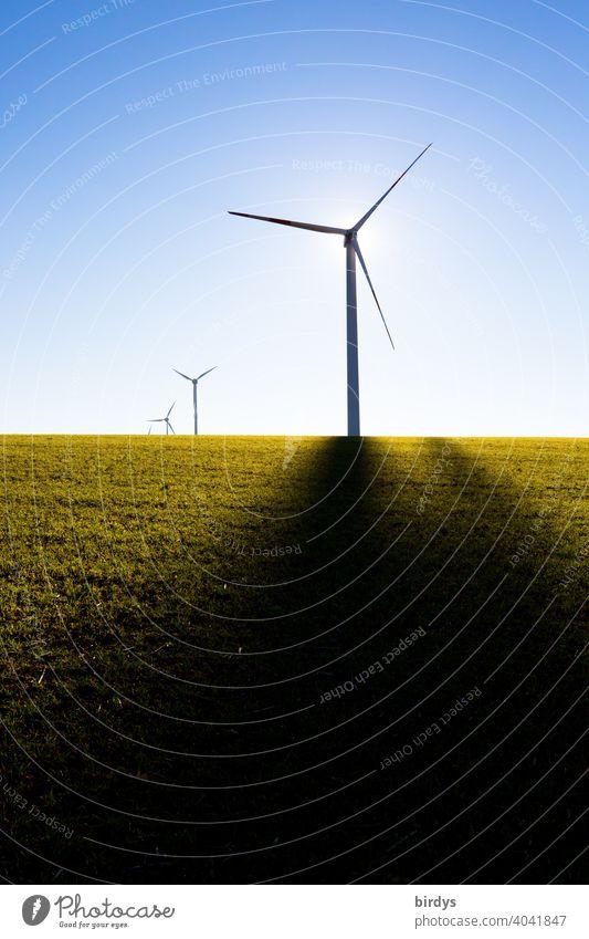 Windkraftanlagen auf dem Feld im Gegenlicht vor blauem Himmel. Schattenwurf von Mast, Sonne hinter dem Generator regenerative energie Erneuerbare Energie