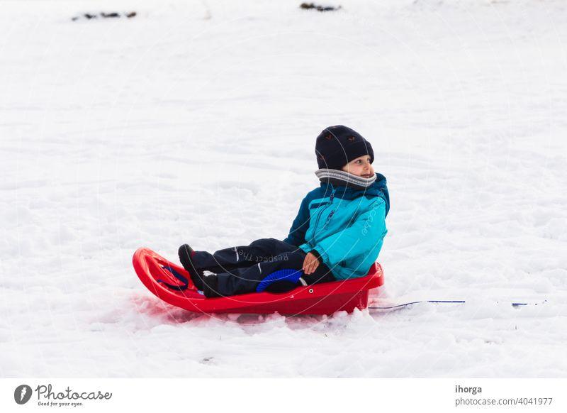 Junge mit rotem Schlitten im Schnee Winter aktiv Kind Kindheit kalt Spaß lustig Fröhlichkeit Glück Hut Feiertag Kinder gestrickt Freizeit wenig Berge u. Gebirge