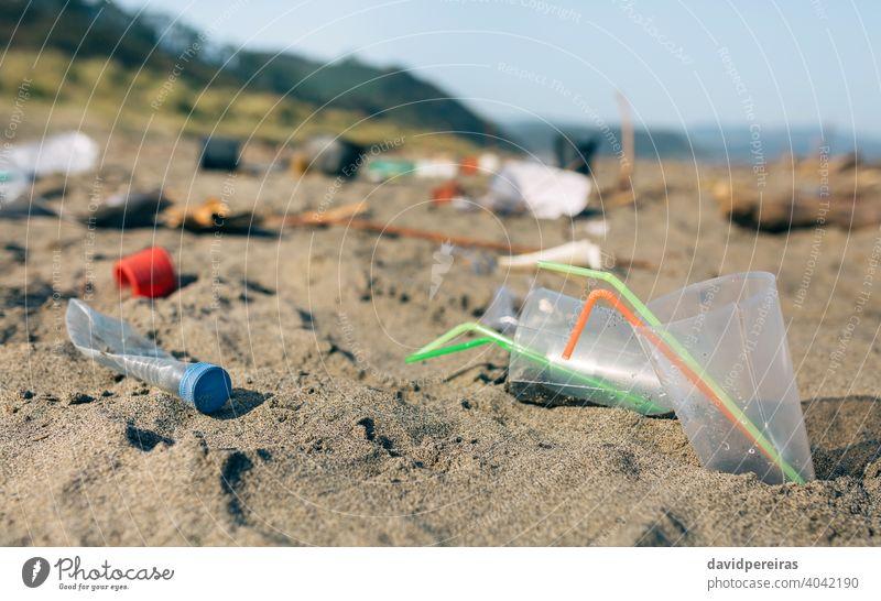 Schmutzige Strandlandschaft voller Müll Strohhalme Einwegbecher Kunststoff kontaminiert Sand dreckig Umwelt Natur Verschmutzung Abfall Küste Kunststoffdeckel
