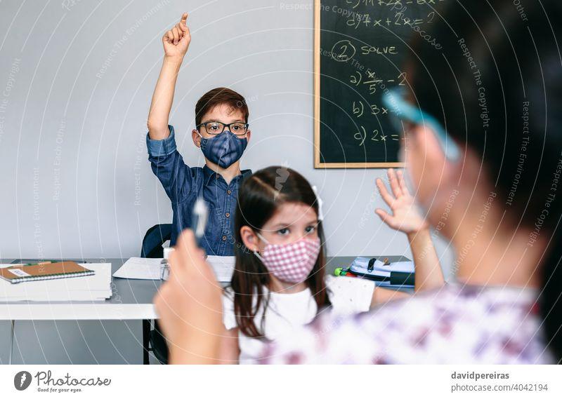Schüler mit Masken heben die Hände in der Schule Handreichung Coronavirus Gesichtsmaske neue Normale teilnehmend Lehrerin Sicherheit Virus Menschen Mädchen