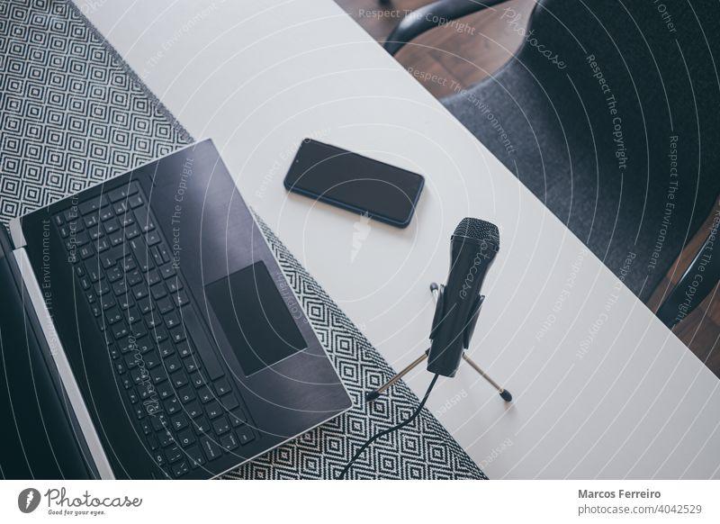 Arbeitsplatz Blogger mit Mikrofon, Laptop und Smartphone. Heimarbeit. Heimarbeitsplatz Heimarbeiter Hausaufgabe Inszenierung Draufsicht Audio Geschäftsmann