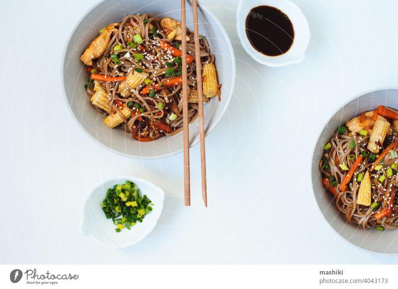 Japanische rühren gebraten Buchweizen Soba-Nudeln mit Huhn und Gemüse - Karotte, Zwiebel und Baby-Mais in Schüssel auf weißem Hintergrund serviert soba
