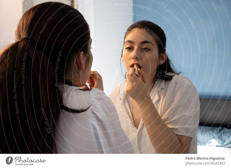 Frau, die in einem Raum Lippenstift auf ihre Lippen aufträgt. Beim Schminken. Blick in den Spiegel Betrachtungen sinnlich Setzen Begierde Kuss weiblich berühren