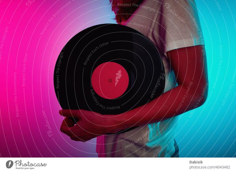 Frau hält Retro-Vinylscheibe mit Neonlicht Scheibe Musik neonfarbig retro altehrwürdig Aufzeichnen Klang Lamelle Album Entertainment Audio schwarz stereo dj