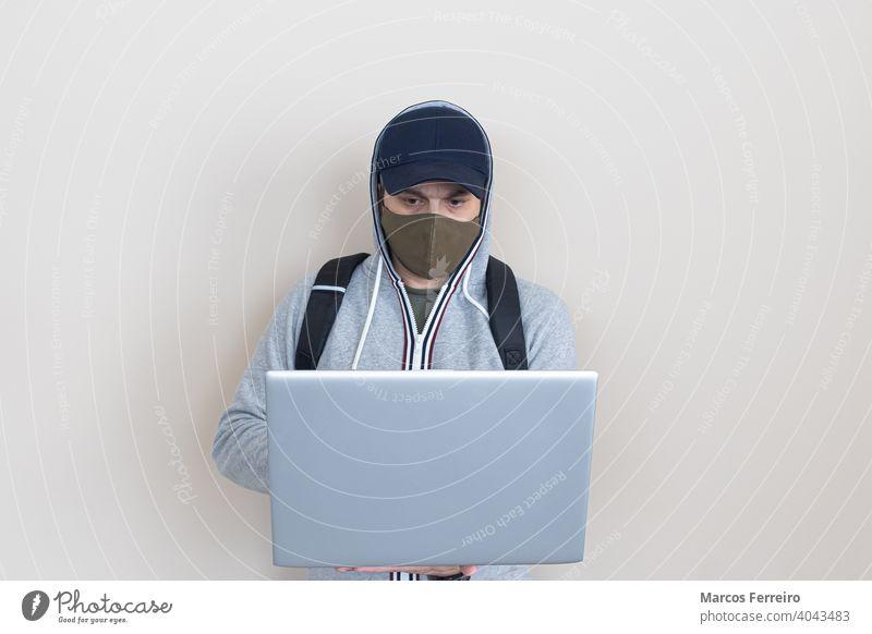 Mann mit Laptop in den Händen und Maske Technik & Technologie Laptop in der Hand Hygiene Virenschutz stehender Geschäftsmann mit Maske Gesichtsmaske
