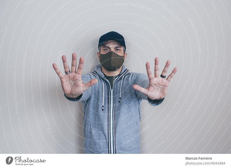 Mann mit Maske stoppt Hände Gesichtsmaske Prävention Kaukasier Ermahnung Sicherheit jung gestikulierend nein Menschen Gefahr Pandemie Seuche Infektion Stehen