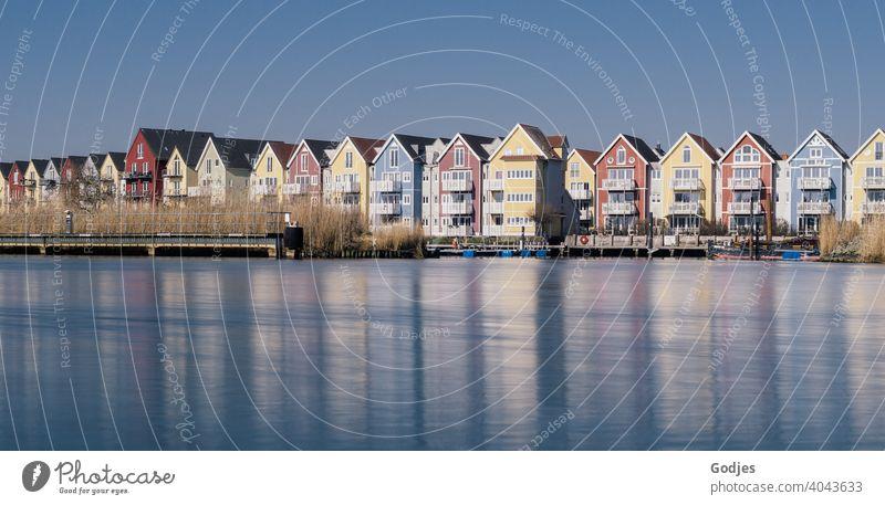 Langzeitbelichtung von bunten Holzhäusern (Schwedenhäuser) mit Bootsanlegern an einem Fluss Gedeckte Farben blau Seeufer Weitwinkel Textfreiraum unten kalt