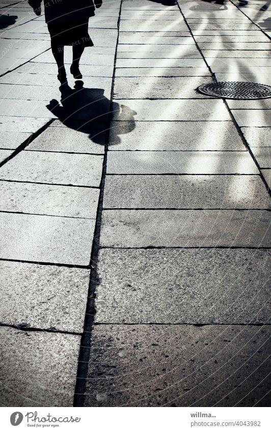 Läuft. Schatten Mensch Person Frau Seniorin gehen Licht und Schatten Boulevard Gehwegplatten Fußgängerzone allein Gullydeckel Spaziergang Erwachsene laufen
