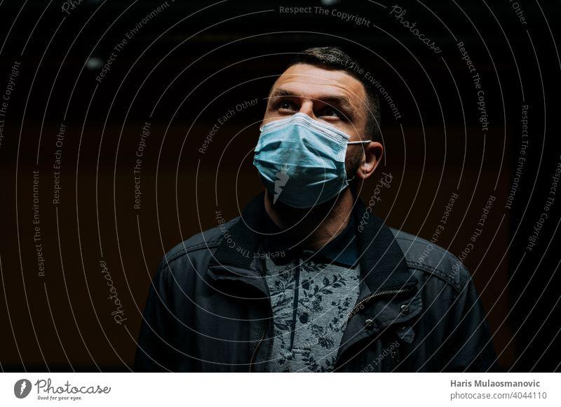 Porträt eines Mannes mit Gesichtsmaske und Blick nach oben auf dunklem schwarzen Hintergrund 19 Erwachsener apokalyptisch schwarzer Hintergrund atmen Kaukasier