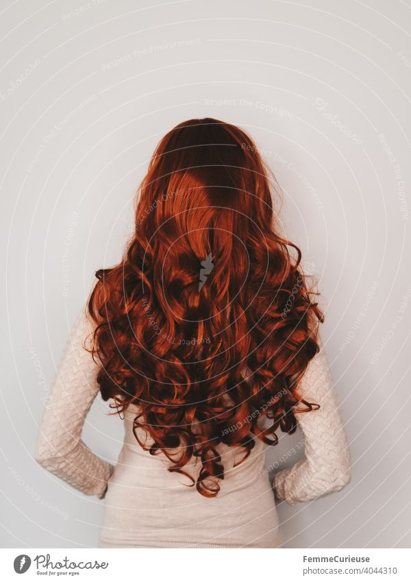 Rückansicht einer Frau mit langen roten lockigen Haaren in hautfarbenem Pullover Schlank lockiges haar feminin gepflegt glänzend Haare & Frisuren Junge Frau