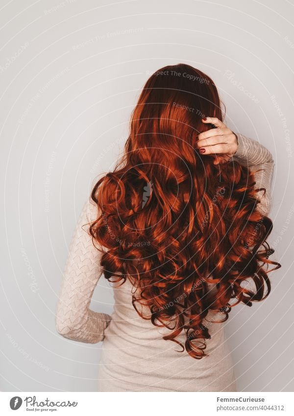 Rückansicht einer Frau mit langen roten lockigen Haaren in hautfarbenem Pullover die sich mit einer Hand ins Haar fasst Neutraler Hintergrund Textfreiraum oben