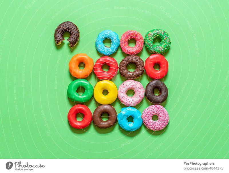 Schokoladen-Donuts mit mehrfarbigem Zuckerguss, Draufsicht auf grünem Hintergrund. obere Ansicht ausgerichtet sortiert gebacken gebissen blau Kuchen farbenfroh