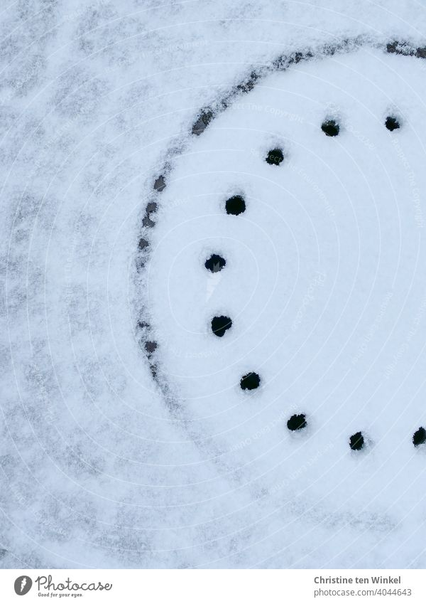 Gullydeckel und Pflastersteine mit Schnee bedeckt. Rand und Löcher des Gullydeckels sind frei von Schnee. Winter Straßenpflaster Wege & Pfade