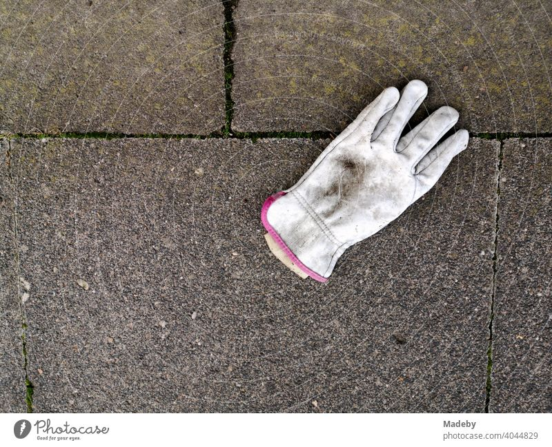 Verschmutzter weißer Arbeitshandschuh auf grauen Steinplatten in Oerlinghausen bei Bielefeld im Teutoburger Wald in Ostwestfalen-Lippe Handschuh Fingerhandschuh