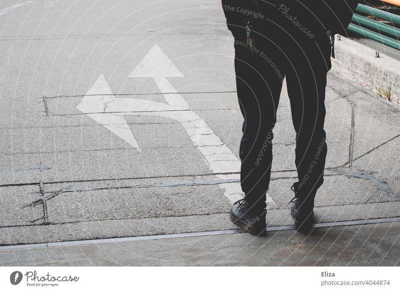 Eine Person steht vor Pfeilen, die in verschiedene Richtungen zeigen. Entscheidungsfindung. Zukunft Weg Orientierung Wegweiser Zukunftsplanung abbiegen Coaching