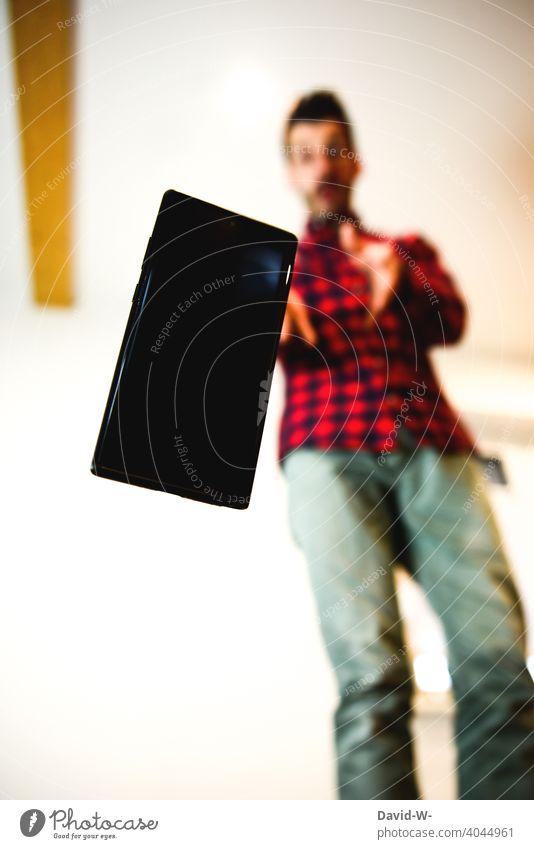 Mann fliegt das Handy aus der Hand Versicherung Sturz kaputt hinfallen haftpflichtversicherung Unfall unachtsam Schaden tollpatschig Gerät