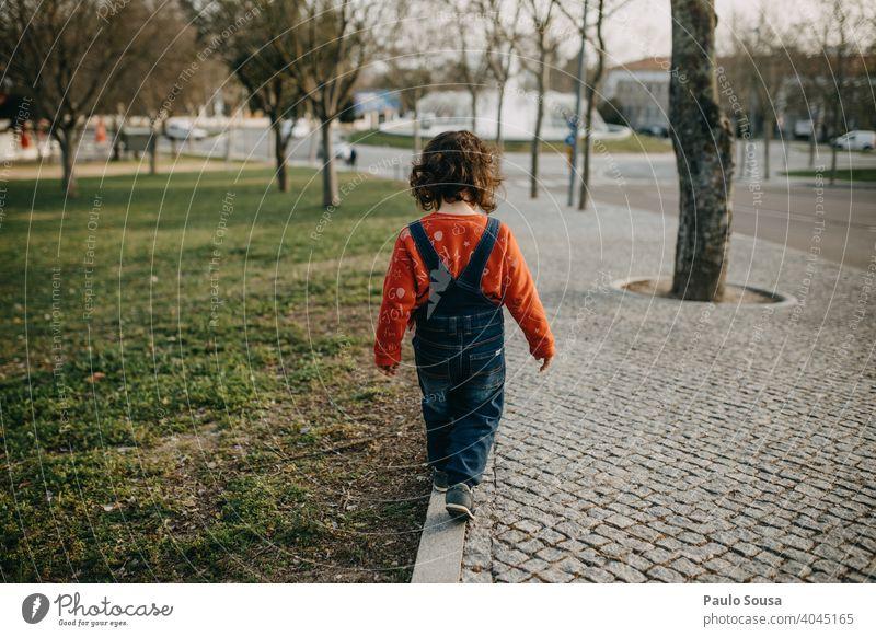 Rückansicht Kind, das auf dem Gehweg läuft Bürgersteig Straßenbelag laufen 1-3 Jahre Spielen Tag Kleinkind Außenaufnahme Mensch Farbfoto Kindheit