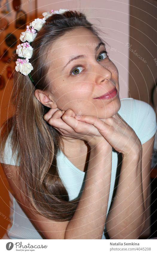 Attraktives junges Mädchen in hellem Kleid und Blumenkranz auf dem Kopf, das mit auf die Hände gestütztem Kopf sitzt und die Kamera in Nahaufnahme betrachtet. Vertikale Ausrichtung.