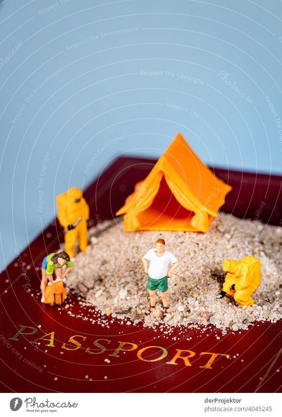 Urlaub unter Coronabedingungen: Miniaturfiguren stehen auf einem Sandhügel auf einem Reisepass Bakterien COVID-19 Virusträger coronavirus Virusinfektion