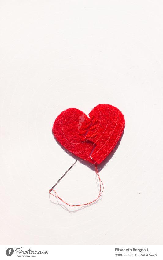 gebrochenes rotes Herz (aus Filz) auf weißem Hintergrund, das mit Nadel und Faden wieder zusammengenäht wird Liebeskummer gebrochenes Herz Herzschmerz