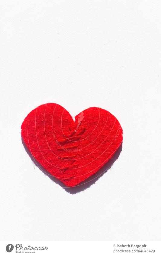 zusammengenähtes rotes Herz (aus Filz) auf weißem Hintergrund Liebeskummer Herzschmerz Scheidung Hoffnung Trennung Trennungsschmerz Reparieren Schmerz