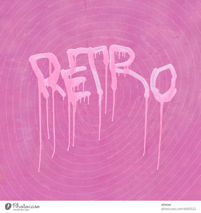 """""""RETRO"""" steht in hellpinken, verlaufenden Druckbuchstaben an einer pinkfarbenen Wand / Graffito / Farbe retro rosa grell Graffiti Jugendkultur Straßenkunst"""