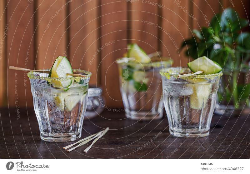Drei Gläser eisgekühltes aromatisiertes Wasser mit Ananas, Gurke, Pfefferminz und gelbem Zuckerrand stehen zum Genießen bereit Getränk Erfrischungsgetränk Glas