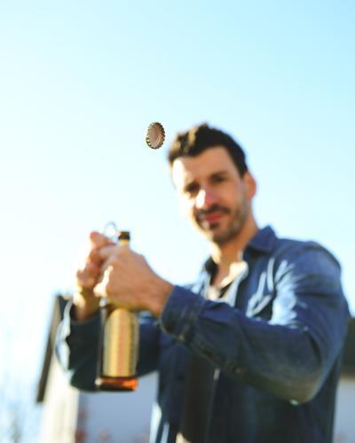 Mann öffnet eine Bierflasche Alkohol öffnen Kronkorken fliegen Flaschenöffner gutes Wetter Sommer gesellschaft Getränk trinken Feste & Feiern Vatertag