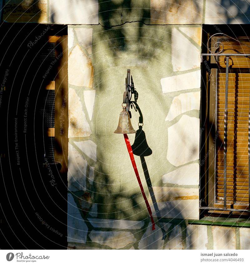 Glocke an der Wand des Hauses Klingel metallisch Schatten Tür Fenster Farbfoto Fassade Menschenleer Außenaufnahme Architektur Eingangstür Häusliches Leben