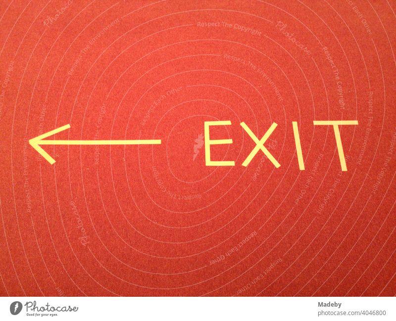 Schriftzug EXIT mit gelbem Pfeil aus Klebeband audf rotem Teppich in einem Museum während der Corona Pandemie in der Hauptstadt Berlin in Deutschland Hinweis