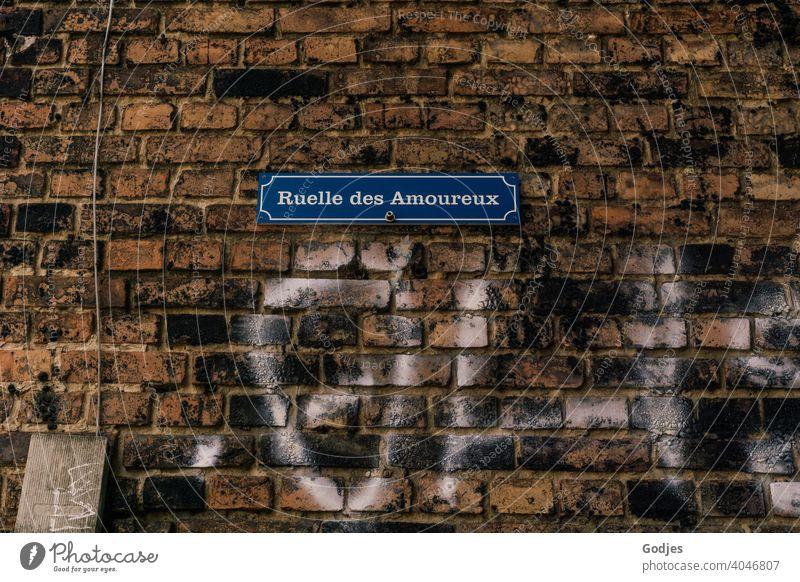 Schild an einer Ziegelwand mit der Beschriftung: Gasse der Liebenden auf Französisch und einem weißen Graffiti Liebhaber Kabel Blau Stromkasten alt technik