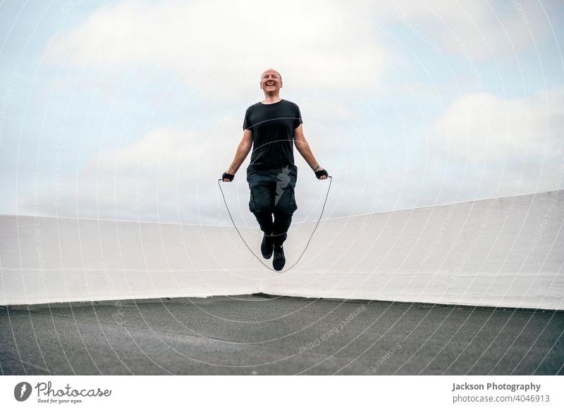 Ein Mann, der während der Abriegelung auf dem Dach mit einem Springseil trainiert Sperrung Sport Dachterrasse Pandemie Seil Hüpfseil Herz Ausdauer seilhüpfen