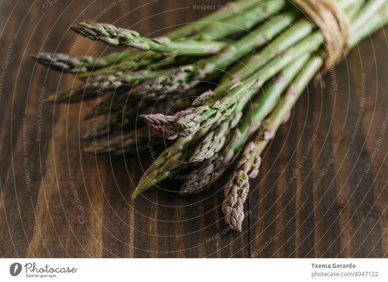Bündel roher, frischer Spargel auf Holztisch. Fokus auf den Vordergrund. Lebensmittel grün Gemüse Gesundheit Hintergrund Diät Paprika Essen Ernährung Mahlzeit