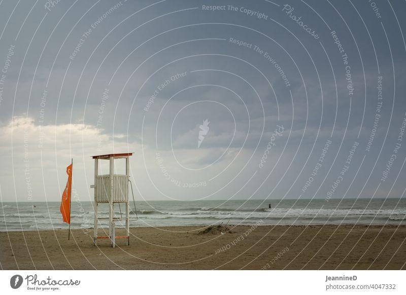 Herbststimmung, leerer Strand mit Bademeisterhaus am Meer mit Regenwolken Regentag Italien Menschenleer schlechtes Wetter Außenaufnahme nass Rimini Farbfoto