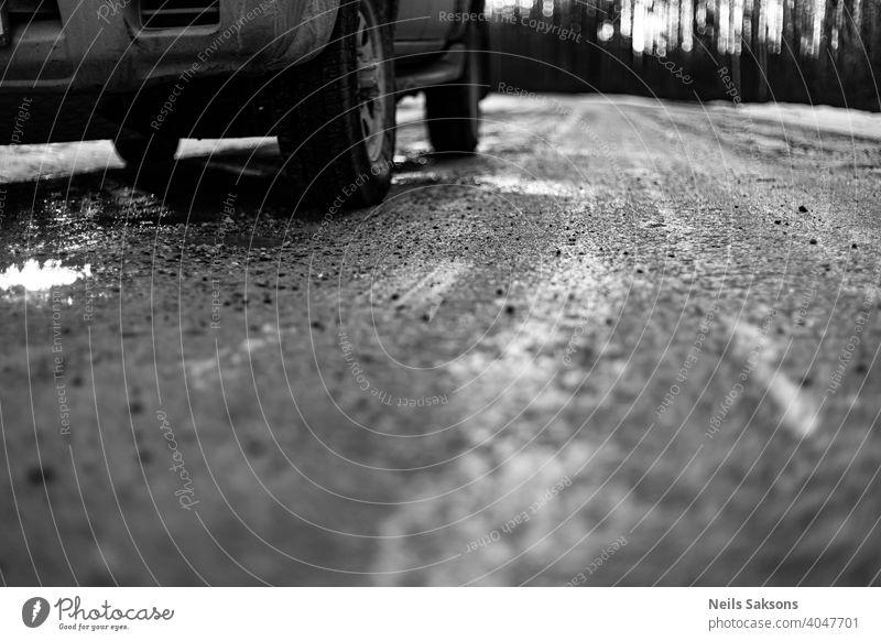 Nahaufnahme von Autoreifen im Winter auf dem Feldweg mit Eis, Schnee und Kies bedeckt unbefestigter Weg Automobil Hintergrund PKW schließen kalt Bedingungen