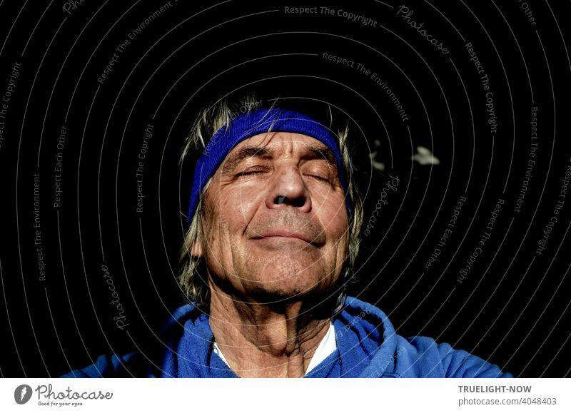 Senior, der dank Pandemie Regeln schon lange seinen Barber Shop nicht mehr aufsuchen konnte, lässt sich von der Frühlings Sonne streicheln, schließt träumend die Augen und macht in blauem Hoodie und Stirnband ein Selfie.