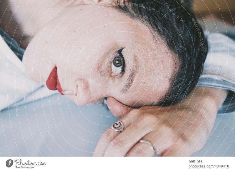 Porträt einer jungen Frau, die ihr Gesicht gegen einen kalten Glastisch lehnt Depression blau traurig mental Gesundheit Psychologie Traurigkeit depressiv weiß