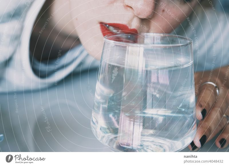 Porträt einer jungen Frau, verdeckt durch ein Glas mit einem transparenten Getränk Depression blau traurig mental Gesundheit Psychologie Traurigkeit depressiv