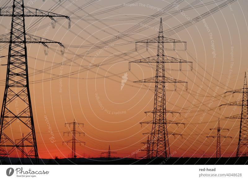 Hochspannungsmasten vor orangerotem Abendhimmel, tiefer Horizont, überkreuzende Leitungen, Masten teilweise angeschnitten Strommast Energie Hochspannungsleitung