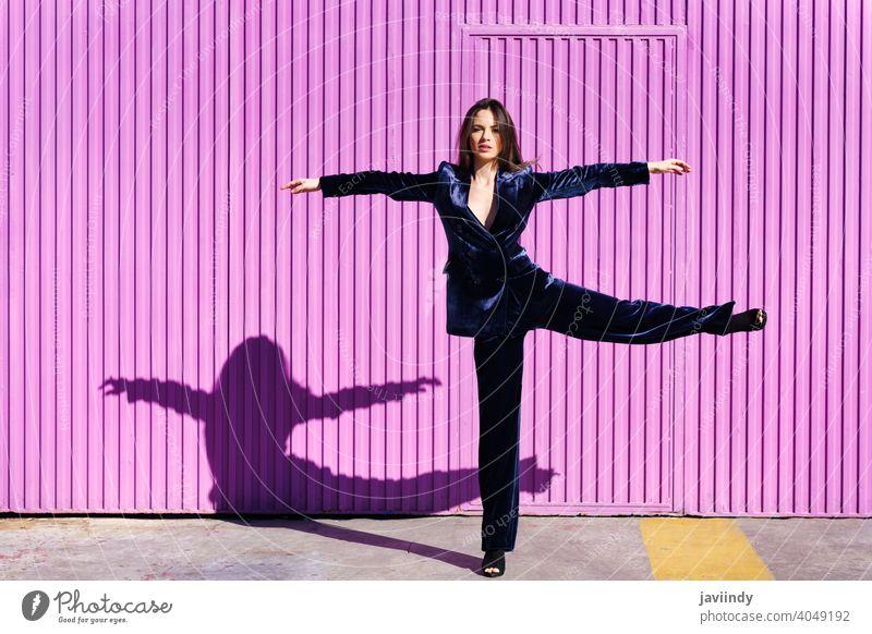 Frau im blauen Anzug tanzt in der Nähe eines rosa Rollladens. Mädchen Waffen Tanzen Bein Person Mode Model Lifestyle urban Hintergrund Dame elegant Gebäude