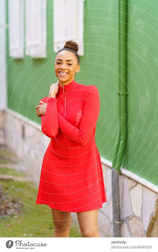 Glückliche schwarze Frau im roten Kleid vor einer grünen Wand Lächeln Schleife Frisur Behaarung Model Schönheit hübsch Porträt Mädchen Fröhlichkeit jung Person