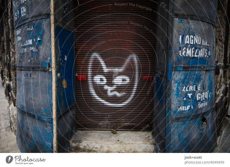 gezeichneter Katzenkopf auf dem Rollladen eines verlassen Ladengeschäfts Geschäft geschlossen geschäftsaufgabe Ecke Beschriftung verwittert retro Spray