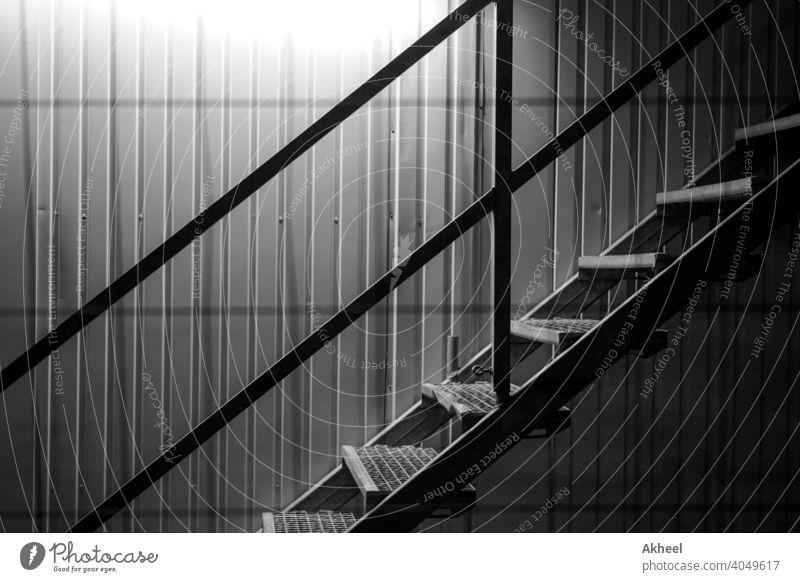 Treppe mit beleuchtetem Hintergrund in einer Baustelle. Schiffscontainer mit Treppe. abstrakt architektonisch Architektur schwarz auf weiß Gebäude Großstadt