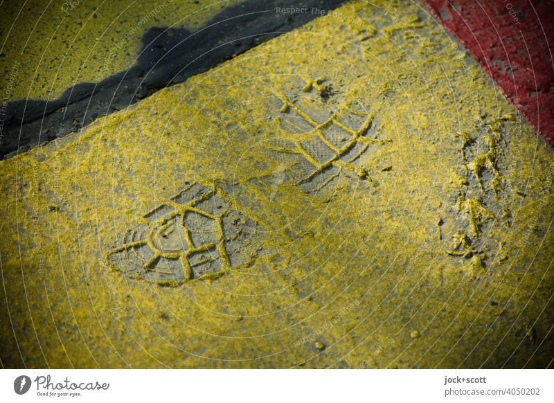 Abdruck eines Schuhs in einer getrockneten Farbschicht Schuhabdruck Spur Strukturen & Formen gelb Halbschatten Hintergrund neutral Hintergrundbild