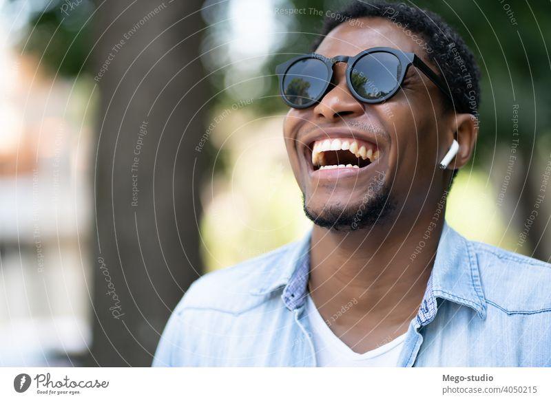 Afroamerikanischer Mann lächelnd beim Gehen im Freien. Afrikanisch Amerikaner Sonnenbrille Großstadt urban Konzept laufen Ohrhörer Lächeln Freude Freizeit