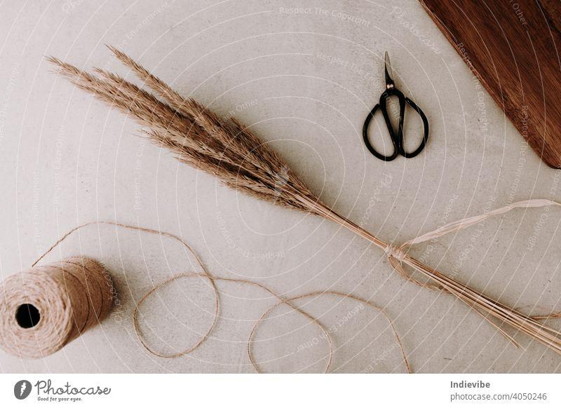Ein Bündel von getrocknetem Gras gebunden mit natürlichen Bast und eine schwarze Schere und eine Rolle von Seil Schnur auf grauem Stein Hintergrund.  Flachlage, Ansicht von oben. Natürliche Farben.