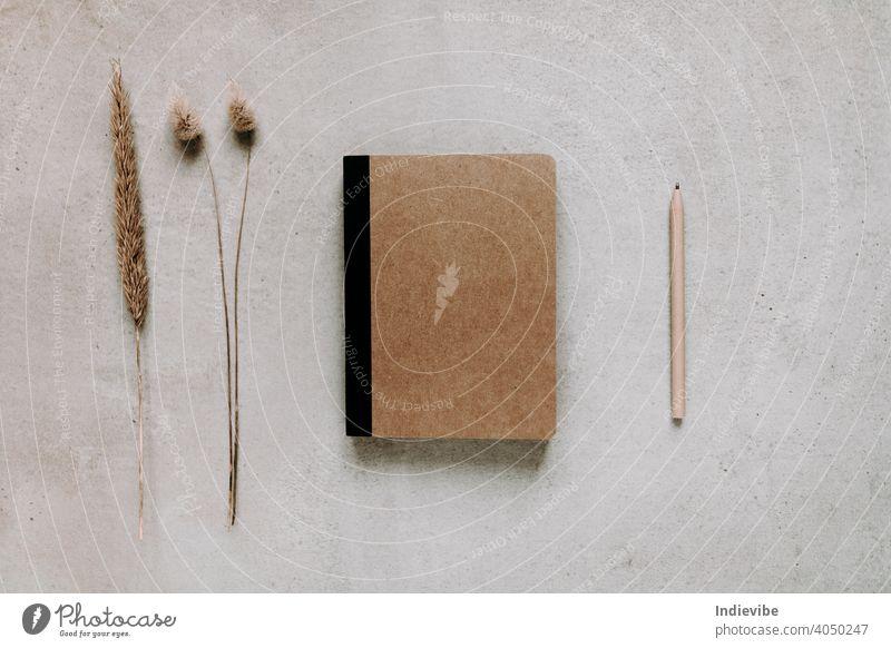 Braunes Papier Notizbuch mit Papier Stift auf grauem Hintergrund. Flat Lay Ansicht von oben. Getrocknete Blumen auf der linken Seite. Moderne Home-Office-Versorgung und Zubehör.