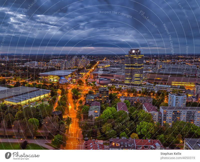 Wunderschöner Dämmerungsblick über das beleuchtete München mit Geschäftsviertel und Autos auf einer Straße aus einer hohen Perspektive. Deutsch Süddeutschland