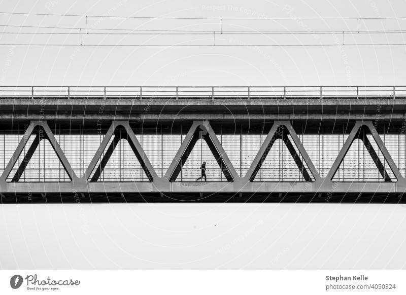 Ein Mann joggt an der Metallkontraktion einer Eisenbrücke Joggen Sport Gesundheit Brücke Athlet Architektur Design Rahmen Konstruktion Silhouette Person Fitness